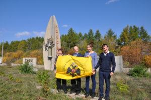Фото с флагом РВИО сделано на фоне знака на въезде в пос. Кассель